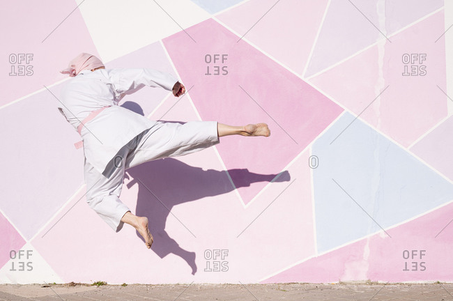 Back view of unrecognizable determined barefooted woman in pink head cover and belt kicking fighting karate in cancer battle concept in the street on pink wall looking away