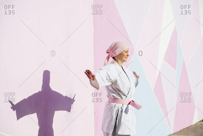 Determined mature woman in pink head cover and belt fighting karate in cancer battle concept in the street on pink wall looking at camera