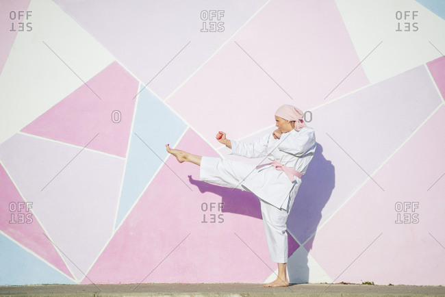 Determined mature barefooted woman in pink head cover and belt kicking fighting karate in cancer battle concept in the street on pink wall looking away