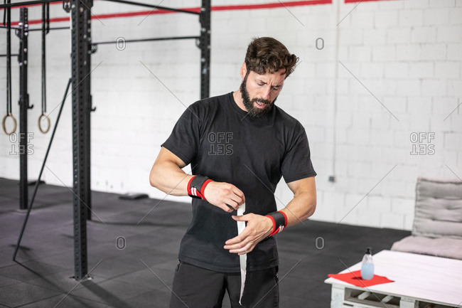 Professional male weightlifter standing in gym and taping fingers while preparing for intense workout