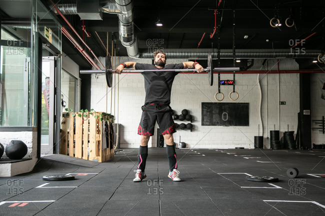 Muscular male athlete doing clean and jerk exercise with barbell during weightlifting training in gym looking at camera