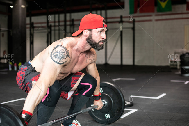 Side view of muscular focused shirtless male athlete doing clean and jerk exercise with barbell during weightlifting training in gym