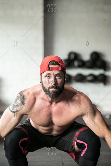 Muscular focused shirtless male athlete doing clean and jerk exercise with barbell during weightlifting training in gym looking at camera