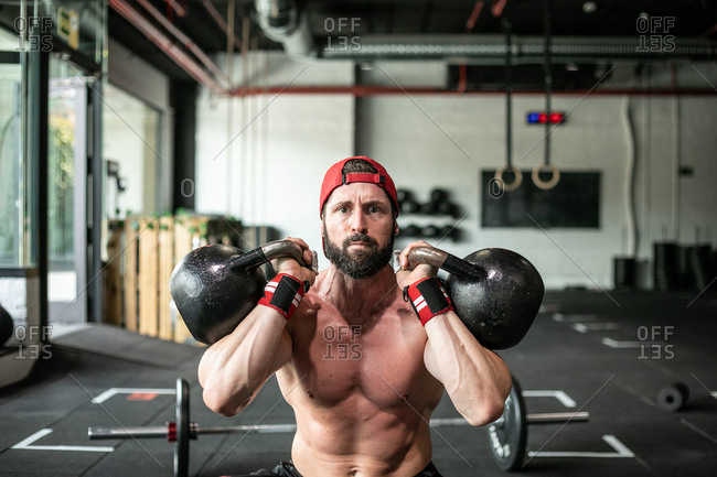 Enduring athletic male with naked torso doing squats with heavy kettlebell while making effort during active training in sports center looking at camera