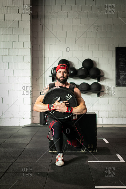 Muscular sportsman in weight vest and with heavy disc doing squats during workout in gym looking at camera
