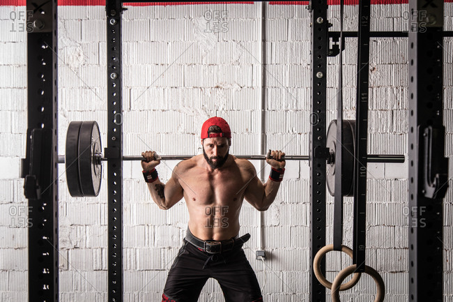 Confident shirtless sportsman standing with heavy barbell and preparing for doing squats during workout in gym
