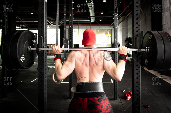 Back view of unrecognizable confident shirtless sportsman standing with heavy barbell and preparing for doing squats during workout in gym