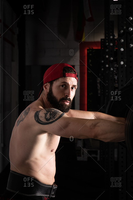 Side view of strong male athlete with naked torso and in weightlifting belt standing near barbell during workout in gym looking at camera