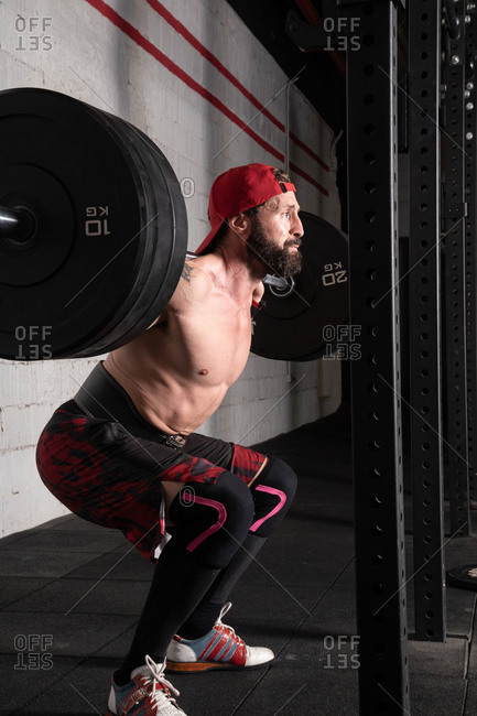 Side view of confident shirtless sportsman standing with heavy barbell and preparing for doing squats during workout in gym