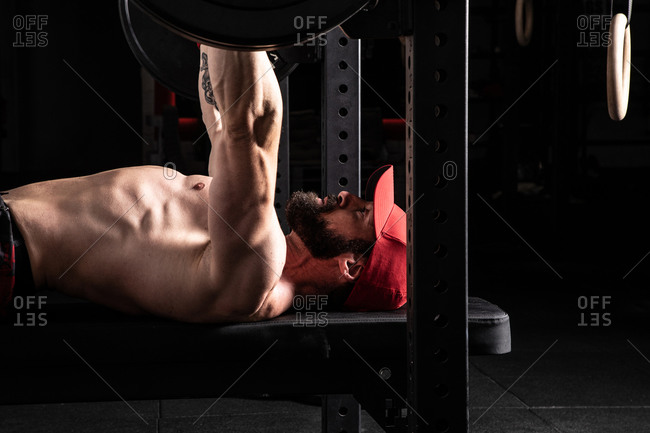 Side view of strong focused male athlete lying on bench press and doing exercises with heavy barbell during workout in gym