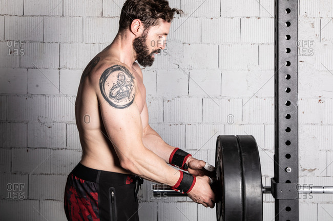 Side view of shirtless muscular male athlete preparing heavy barbell for weightlifting workout in sports club