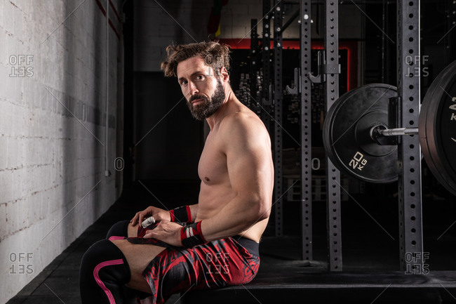 Side view of determined sportsman with strong naked body sitting on bench press with barbell and getting ready for workout looking at camera