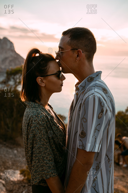 Side view of passionate couple hugging and kissing while standing on hill on background of sunset over sea