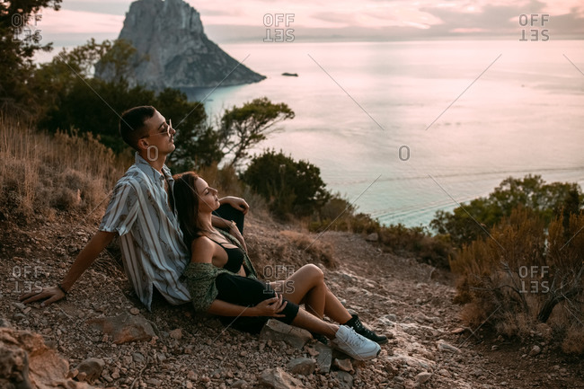 Side view of tranquil couple cuddling and sitting on stony shore while admiring sunset over sea in summer and looking away