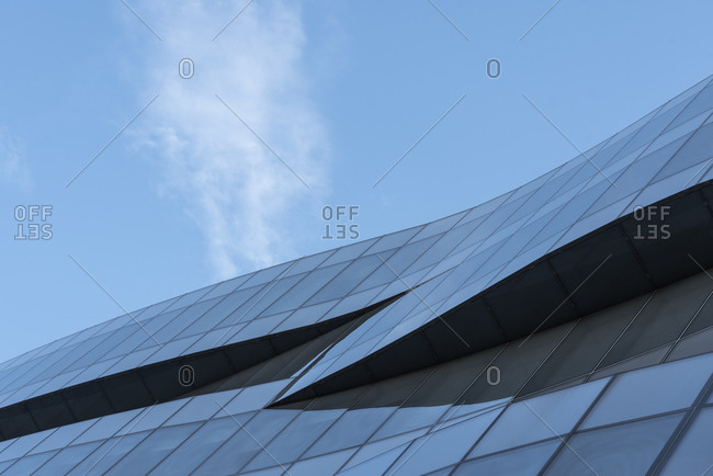 From below of futuristic building with wave shaped exterior made of glass panels located against blue sky in city center