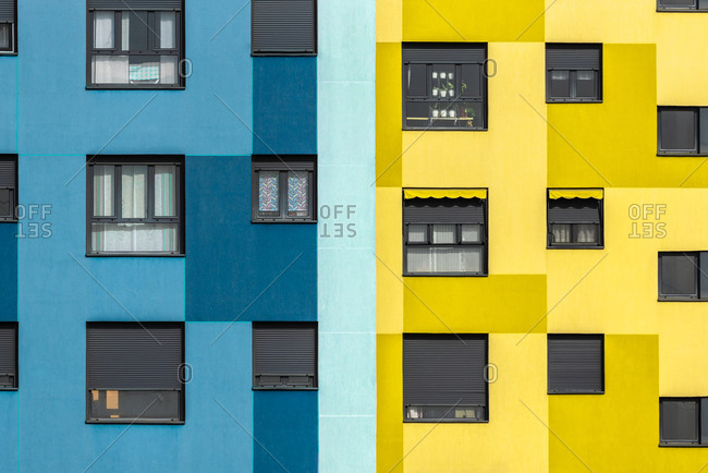 Background of blue and yellow exterior of residential building with windows of various sizes in city