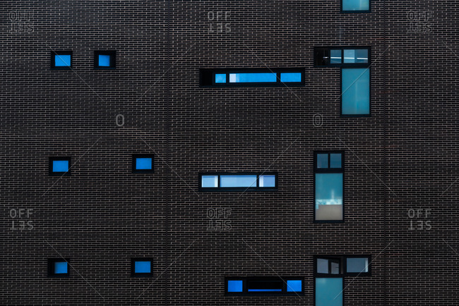 Abstract background of detail of modern building with dark wall with windows of different shapes and sizes