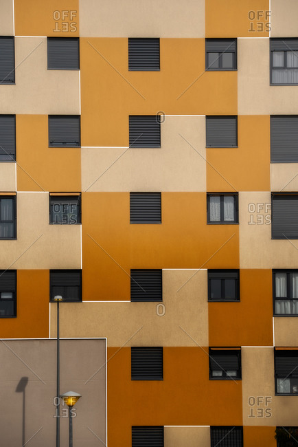 Background of orange exterior of residential building with windows of various sizes in city