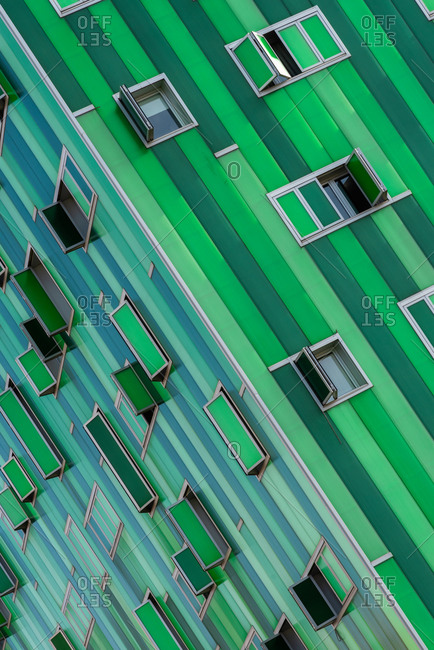 Corner of part of contemporary building with vivid green facade and opened windows