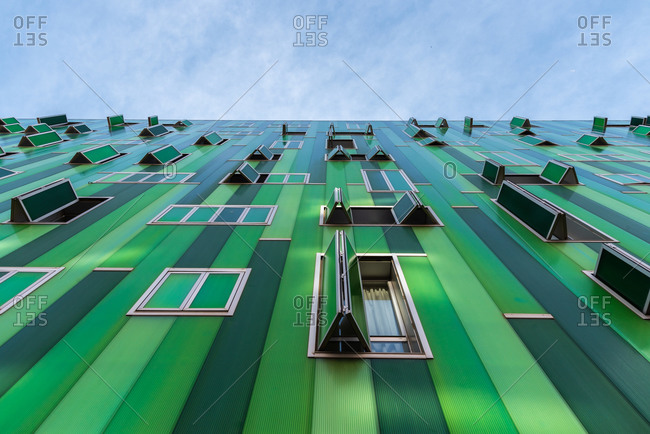 From below contemporary building with vivid green facade and opened windows on blue sky