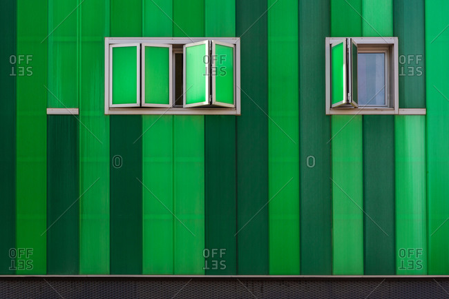 Contemporary building with vivid green facade and opened windows