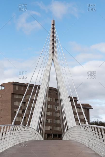 Contemporary suspension footbridge with long steel cables on background on building in city