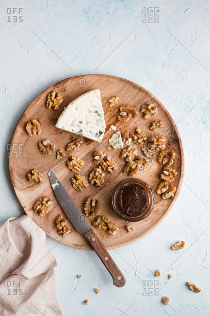 Top view of appetizing blue cheese and walnuts prepared on wooden board in kitchen for cooking tasty homemade cheesecake
