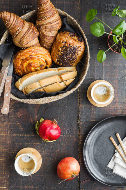 Top view of arrangement of buns and cups of coffee on wooden table for delicious breakfast at home