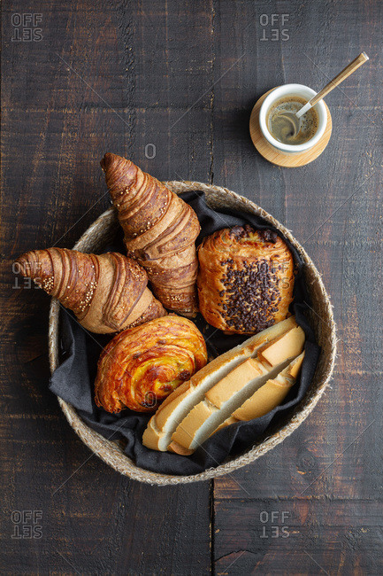 Top view of basket full of delicious homemade croissants and buns on wooden table at home