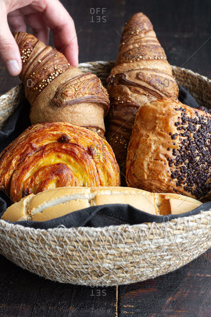 Crop person with basket full of delicious homemade croissants and buns on wooden table at home