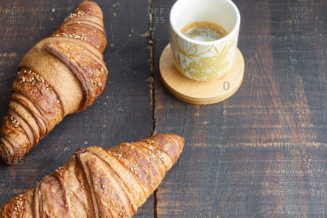 High angle of sweet croissants arranged on wooden table with cup of aromatic coffee for breakfast at home
