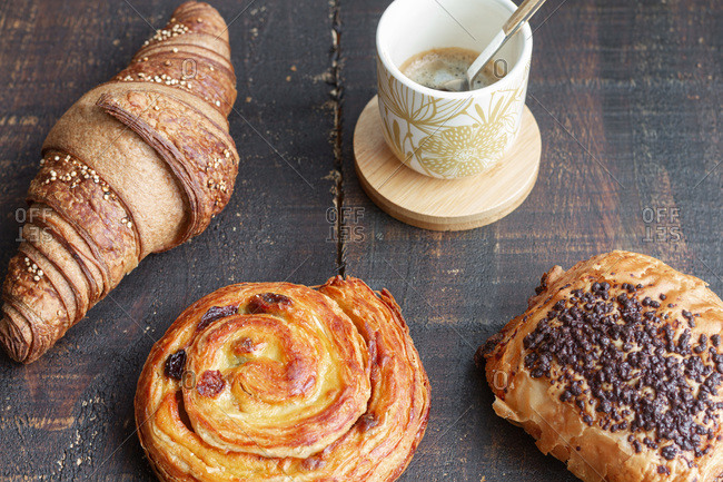 Top view of delicious homemade croissants arranged on wooden table with tasty bun with chocolate and roll with raisin