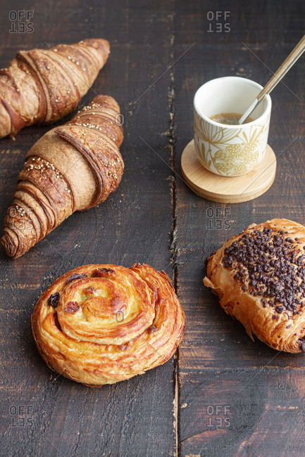 From above delicious homemade croissants arranged on wooden table with tasty bun with chocolate and roll with raisin