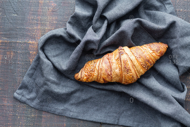 From above of delicious croissant placed on piece of textile of wooden table in cafe