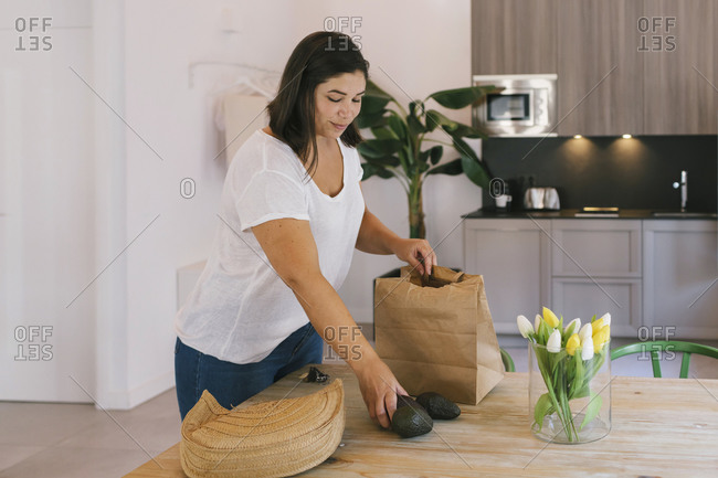 A woman is taking out some food from the shopping bag. There are avocados and she is in the kitchen.