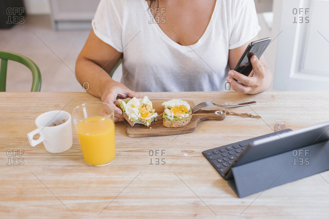 Unrecognizable woman with breakfast and smart devices for work from home