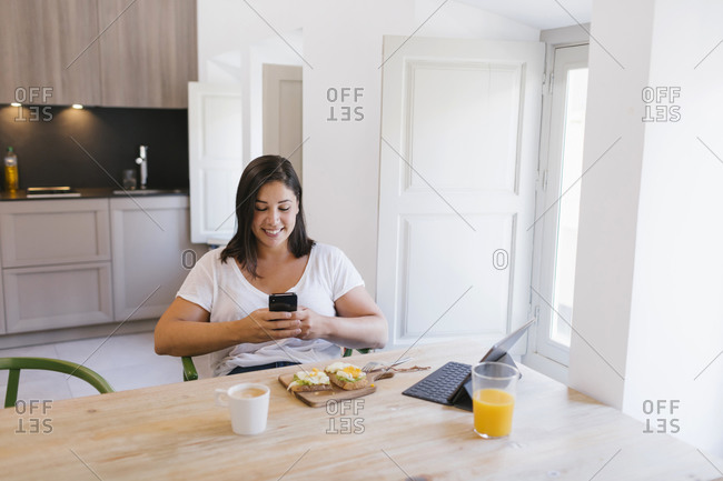 Woman typing in a smartphone and with a healthy breakfast