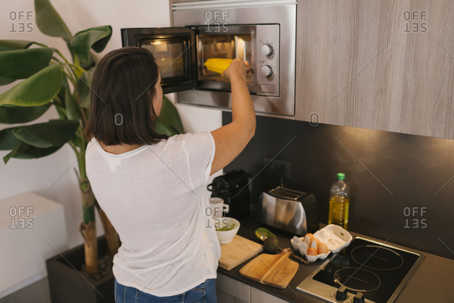 Woman using a microwave for cooking. Unrecognizable person.