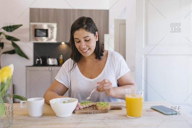Smiley woman preparing healthy breakfast with avocado toasts and orange juice