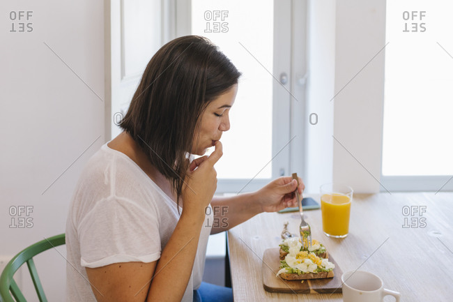 Happy woman tasting some avocado with finger in dining table