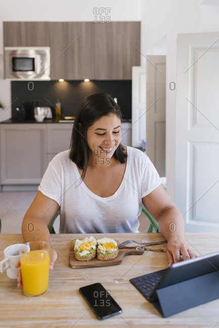Smiley woman working and having a healthy breakfast in home