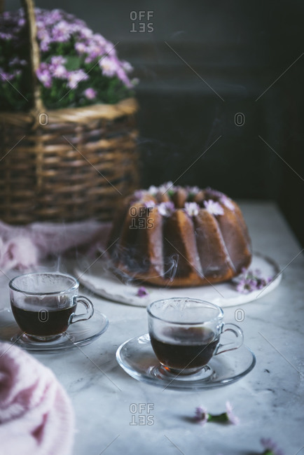 High angle of hot tea in glass cups arranged on table with delicious lemon Bundt cake