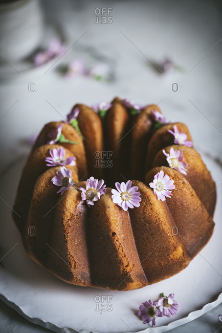 From above of tasty Bundt cake decorated with fresh flowers and served on plate on table in kitchen