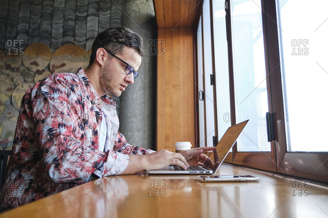 Young focused male freelancer with eyewear and disposable glass of hot drink sitting at windowsill with netbook