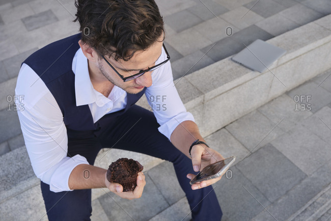 From above of crop businessman in stylish apparel with cupcake text messaging on cellphone while sitting on stairs