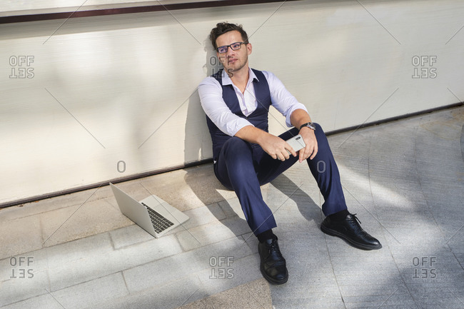 From above of young masculine office worker in formal suit and eyewear sitting on floor near wall with cellphone and netbook