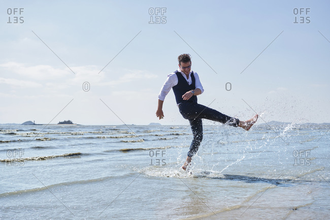 Young happy barefoot office worker standing with raised leg while playing with splashing sea water under cloudy sky