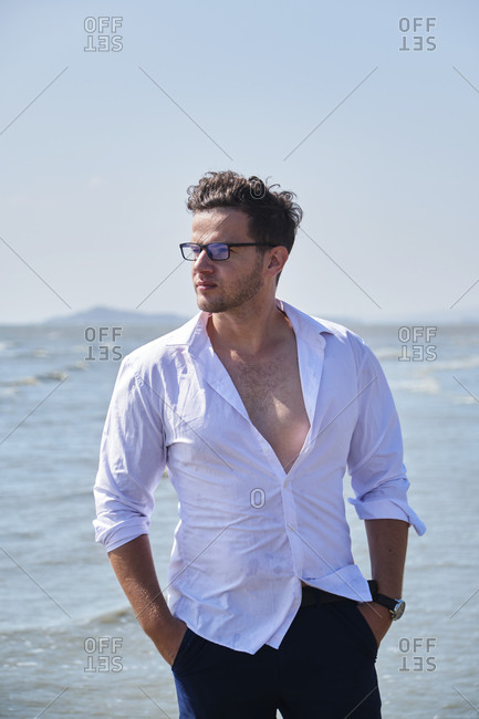 Young handsome male in trendy apparel and eyewear looking away with hands in pockets behind wavy sea under sky
