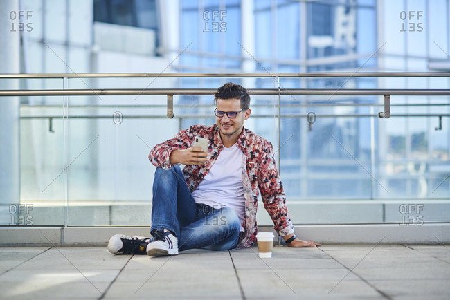 Young smiling male in stylish wear and eyeglasses chatting on cellphone while sitting with crossed legs on floor near glass wall and takeaway coffee