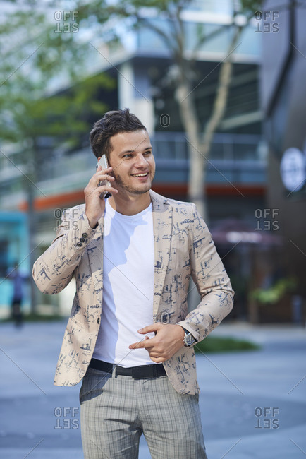 Young cheerful male in trendy apparel talking on cellphone while looking away in town